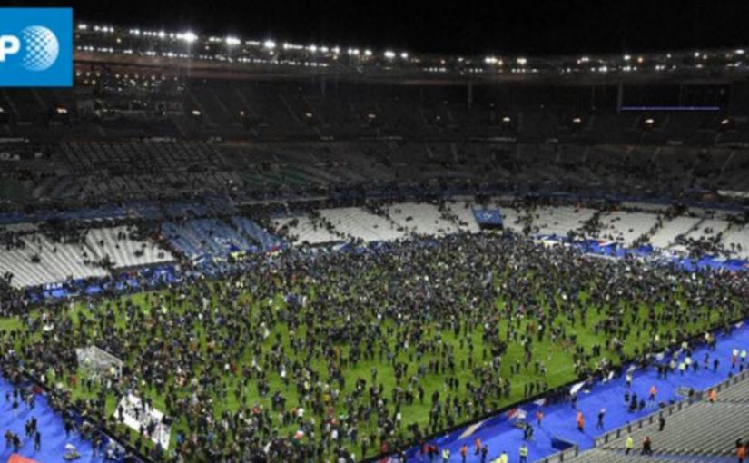 Spectators sing the French national anthem while evacuating stadium